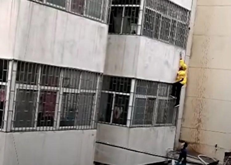 Repartidor escala edificio para sostener a niña que colgaba desde un tercer piso