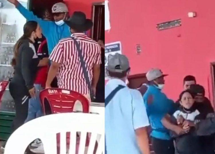 La mujer le grita enojada a su pareja, mientras que otras dos personas le piden retirarse del sitio.